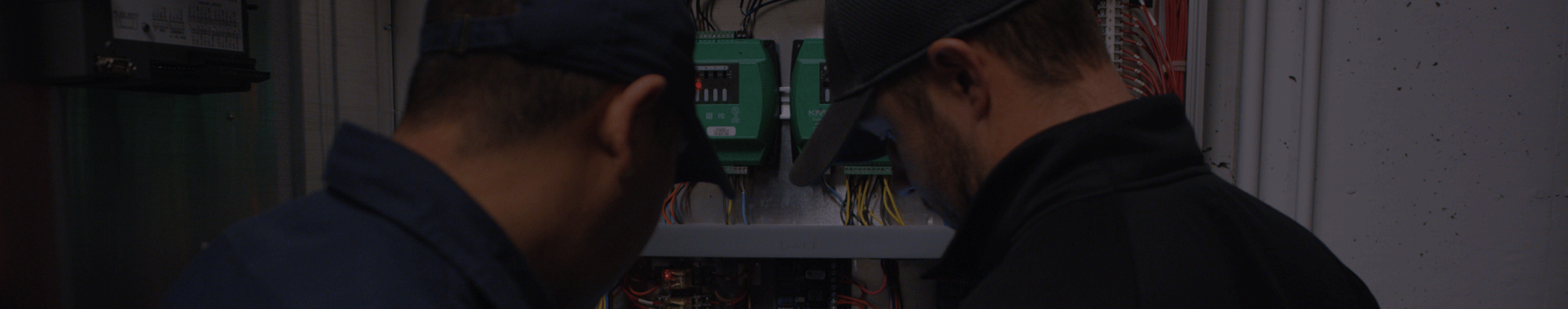 two workers working on a building control system